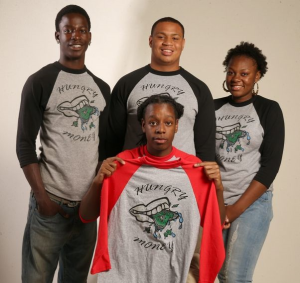 From left, standing, Darius White, Damon Jackson and Hanifah Habeeb, and Damon White, seated, display a T-shirt. Charles Lewis/Buffalo News
